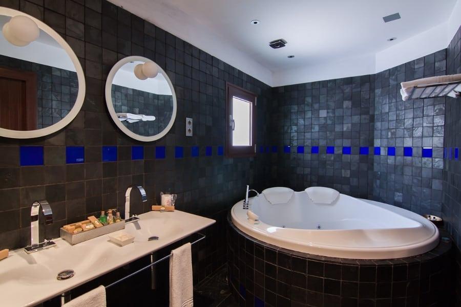 Baño equipado con jacuzzi y ducha con rociador tipo lluvia